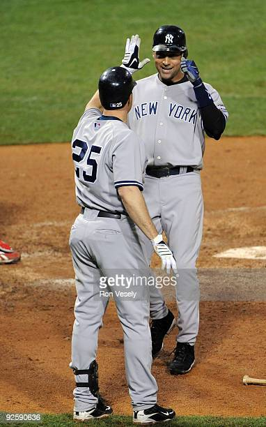 Derek Jeter of the New York Yankees is congratulated by Mark Teixeira after scoring on Johnny Damon's double in the top of the fifth inning during...