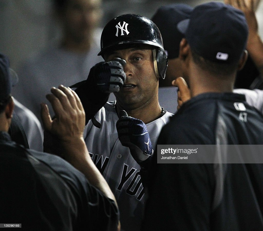 Derek Jeter #2 of the New York Yankees is congratulated by teammates in the dugout after scoring in the 3rd inning against the Chicago White Sox at U.S. Cellular Field on August 3, 2011 in Chicago, Illinois.