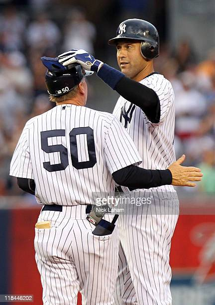 Derek Jeter of the New York Yankees is greeted by first base coach Mick Kelleher on second base after hitting a double in the first inning for career...