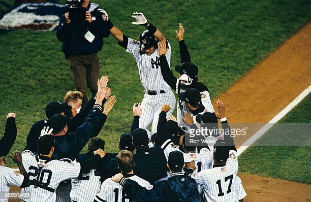 Derek Jeter of the New York Yankees is mobbed by teammates after hitting a game winning home run in the bottom of the tenth inning off of ByunHyun...
