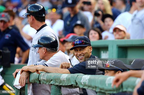 Derek Jeter of the New York Yankees looks on from the dugout against the Boston Red Sox during the last game of the season at Fenway Park on...