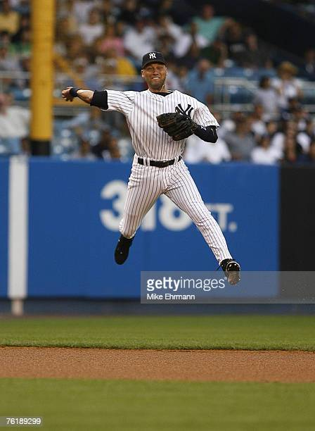 SS Derek Jeter of the New York Yankees makes a jumping throw to first to try to put out Pete Orr on an infield single in the first inning during a...