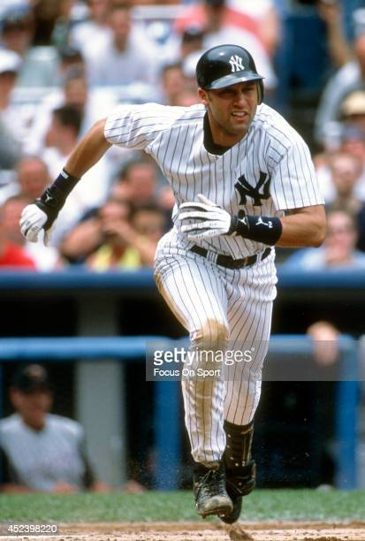 Derek Jeter of the New York Yankees puts the ball in play and runs towards first base during an Major League Baseball game circa 2002 at Yankee...