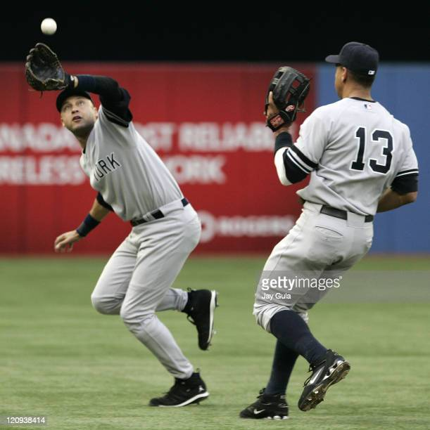 Derek Jeter of the New York Yankees ranges back into left field to snare this popup as Alex Rodriguez looks on in action vs the Toronto Blue Jays at...