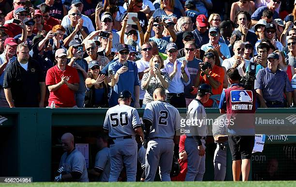 Derek Jeter of the New York Yankees returns to the dugout after batting in the third inning against the Boston Red Sox during a game at Fenway Park...