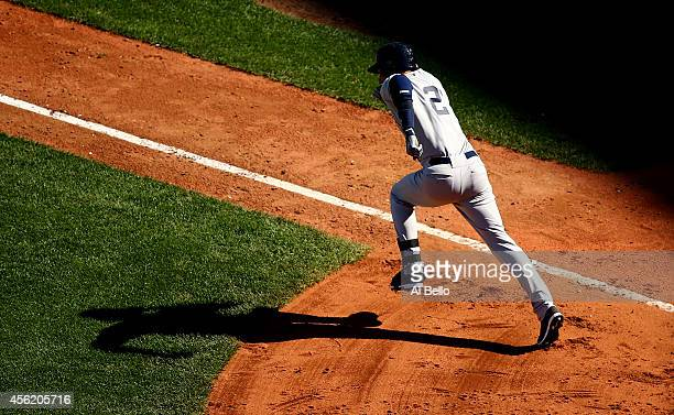 Derek Jeter of the New York Yankees runs to first base after a hit in the third inning against the Boston Red Sox during a game at Fenway Park on...