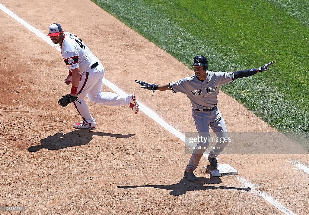 Derek Jeter #2 of the New York Yankees signals that he is safe at first base after beating a throw to Adam Dunn in the 2nd inning against the Chicago White Sox in the 1st inning U.S. Cellular Field on May 25, 2014 in Chicago, Illinois.