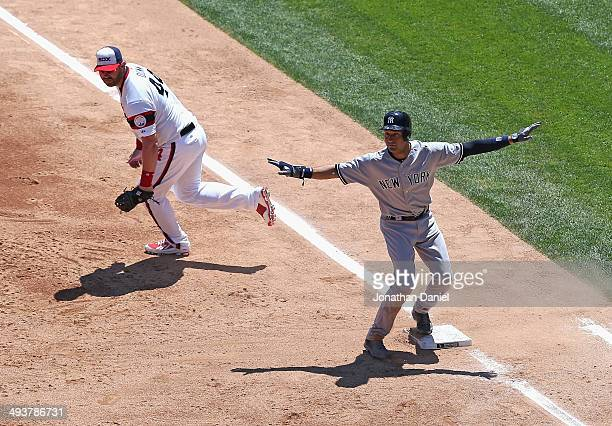 Derek Jeter of the New York Yankees signals that he is safe at first base after beating a throw to Adam Dunn in the 2nd inning against the Chicago...