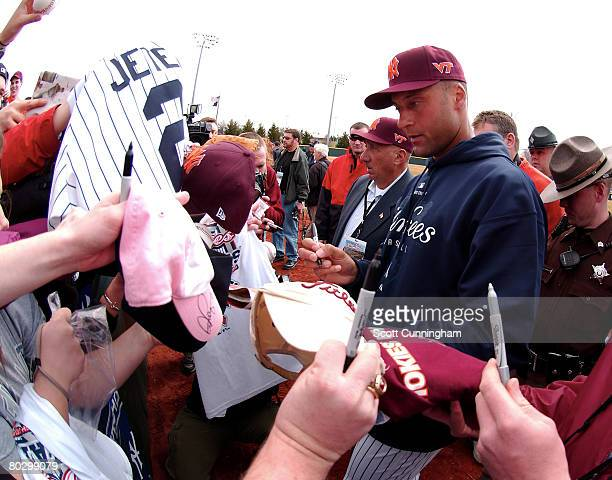 Derek Jeter of the New York Yankees signs autographs before a memorial exhibition game against the Virginia Tech Hokies at English Field on March 18...