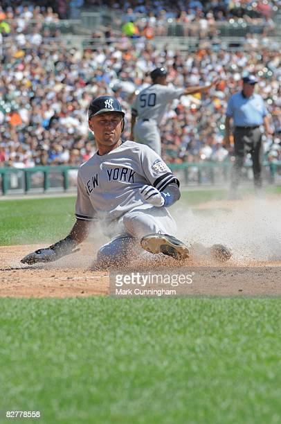Derek Jeter of the New York Yankees slides safely into home during the game against the Detroit Tigers at Comerica Park in Detroit Michigan on...