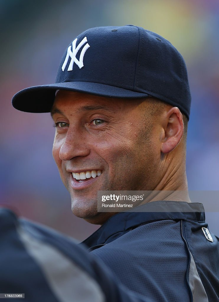 Derek Jeter #2 of the New York Yankees smiles in the dugout during play against the Texas Rangers at Rangers Ballpark in Arlington on July 22, 2013 in Arlington, Texas.