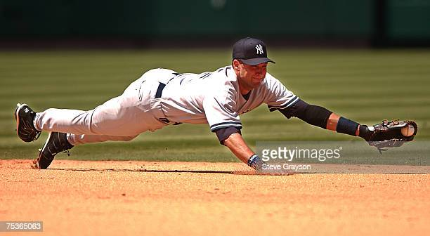 Derek Jeter of the New York Yankees snares a line drive to rob the Los Angeles Angels of an extra base hit during their contest at Angels Stadium in...
