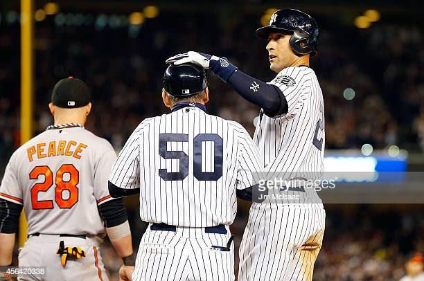 Derek Jeter of the New York Yankees stands at first base in seventh inning against the Baltimore Orioles with first base coach Mick Kelleher at...