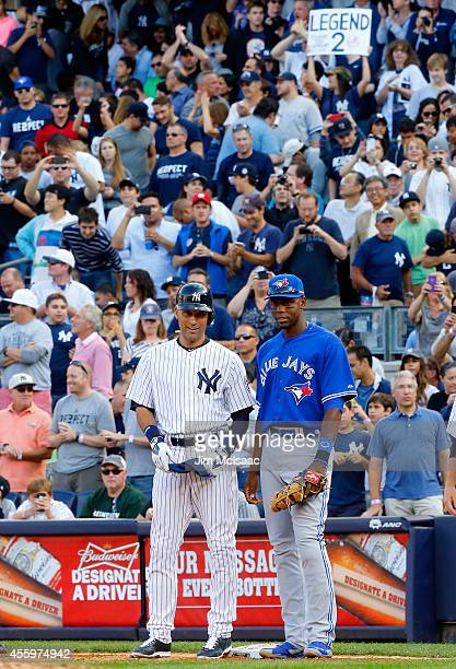 Derek Jeter of the New York Yankees stands at first base with with John Mayberry Jr #9 of the Toronto Blue Jays after a third inning base hit at...