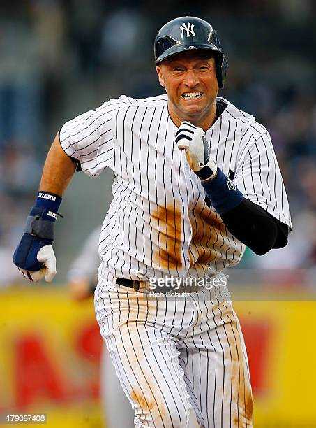 Derek Jeter of the New York Yankees tags up and runs to third base on a sacrifice fly by Robinson Cano in the first inning scoring teammate Brett...