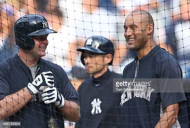 Derek Jeter of the New York Yankees talks to Brian McCann during batting practice with Ichiro Suzuki behind him before the start of MLB game action...