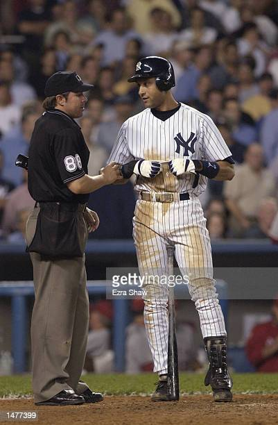 Derek Jeter of the New York Yankees talks with umpire Doug Eddings at the plate during game two of the American League Division Series against the...