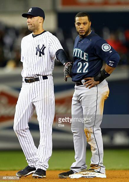 Derek Jeter of the New York Yankees taps Robinson Cano of the Seattle Mariners as Cano stands on second base on April 29 2014 at Yankee Stadium in...