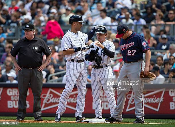 Derek Jeter of the New York Yankees taps the helmet of first base coachMick Kelleher during the game against the Minnesota Twins at Yankee Stadium on...