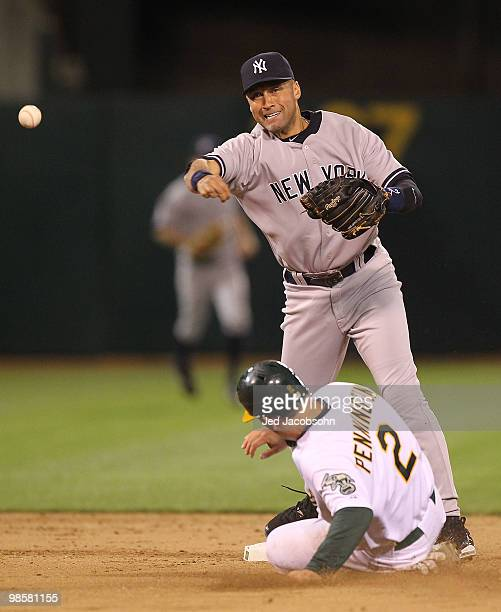 Derek Jeter of the New York Yankees throws to first as Cliff Pennington of the Oakland Athletics slides into second on a double play ball hit by...