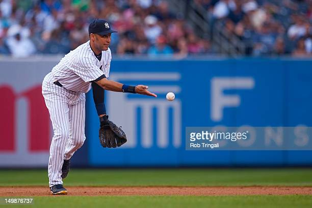 Derek Jeter of the New York Yankees tosses a ball towards second base for the force out during the game against the Boston Red Sox on Saturday July...