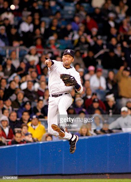Derek Jeter of the New York Yankees tries to throw out Brandon Inge of the Detroit Tigers during their game at Yankee Stadium on May 25 2005 in the...