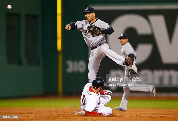 Derek Jeter of the New York Yankees turns the double play at second base over Jonny Gomes of the Boston Red Sox in the second inning during the game...