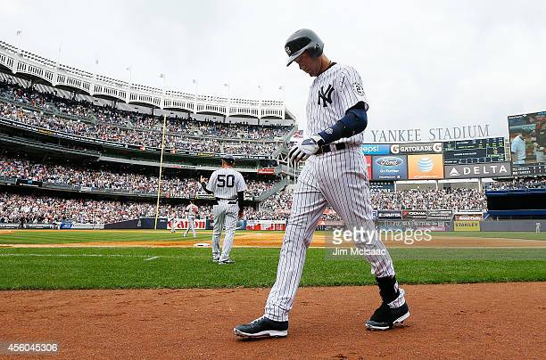 Derek Jeter of the New York Yankees walks back to the dugout after grounding out in the eighth inning against the Baltimore Orioles at Yankee Stadium...