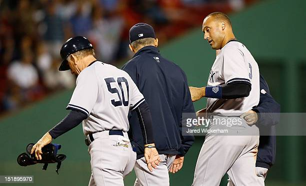 Derek Jeter of the New York Yankees walks off of the field with first base coach Mick Kelleher and manager Joe Girardi after injuring himself on a...