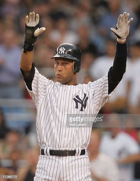 Derek Jeter of the New York Yankees waves in Jason Giambi in the first inning against the Florida Marlins on June 23 2006 at Yankee Stadium in the...