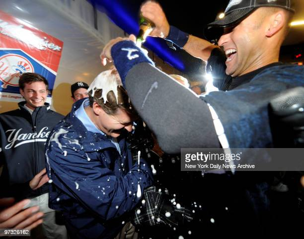 Derek Jeter pours champagne on Hal and Jennifer Steinbrenner in the club house as New York Yankees celebrate after winning the ALCS with 52 win...