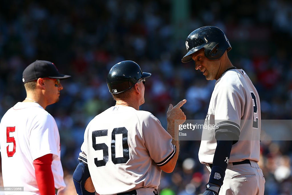 Derek Jeter #2 speaks with Mick Kelleher #50 of the New York Yankees after hitting a single for his last career at bat in the third inning against the Boston Red Sox during the last game of the season at Fenway Park on September 28, 2014 in Boston, Massachusetts.