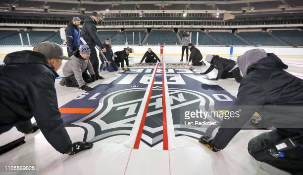 Derek King NHL Senior Manager Facilities Operations Hockey Operations with his ice crew install the center ice logo in preparation for the 2019 Coors...