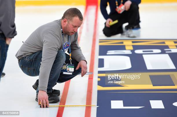 Derek King NHL Senior Manager of Facility Operations installs the center ice logo during buildout for the 2017 Coors Light NHL Stadium Series at...