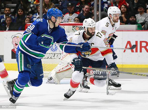 Derek MacKenzie and Aaron Ekblad of the Florida Panthers and Brendan Gaunce of the Vancouver Canucks watch the play during their NHL game at Rogers...