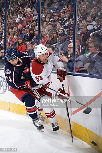 Derek MacKenzie of the Columbus Blue Jackets and Derek Morris of the Phoenix Coyotes battle as they skate after a loose puck during the third period...