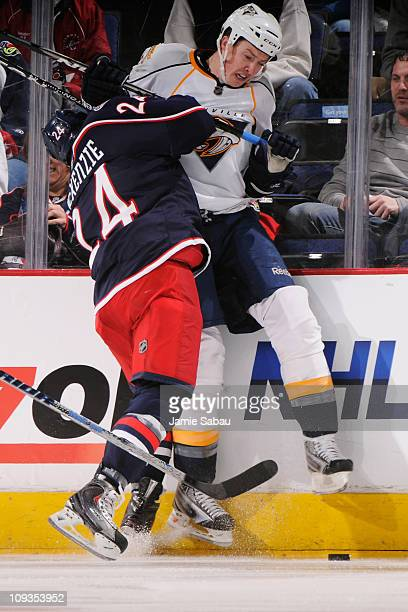 Derek MacKenzie of the Columbus Blue Jackets checks Jerred Smithson of the Nashville Predators into the boards during the first period on February...