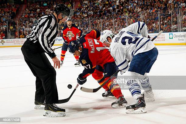 Derek MacKenzie of the Florida Panthers faces off against Peter Holland of the Toronto Maple Leafs at the BBT Center on December 28 2014 in Sunrise...