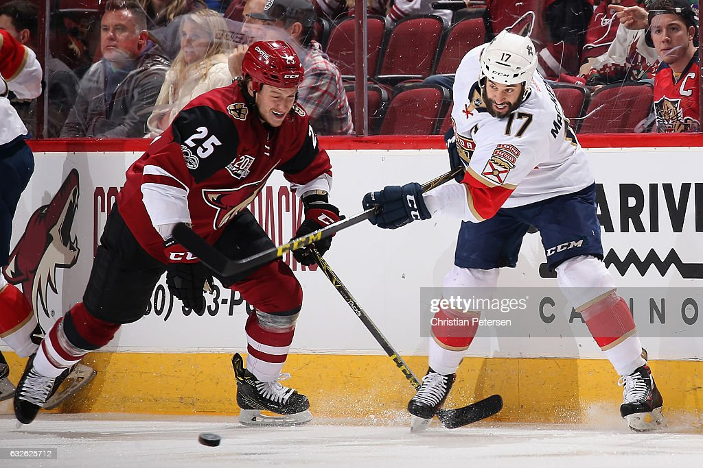 Derek MacKenzie #17 of the Florida Panthers passes the puck ahead of Ryan White #25 of the Arizona Coyotes during the first period of the NHL game at Gila River Arena on January 23, 2017 in Glendale, Arizona. The Coyotes defeated the Panthers 3-2 in overtime.