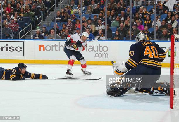 Derek MacKenzie of the Florida Panthers shoots the puck against Taylor Fedun and Robin Lehner of the Buffalo Sabres during an NHL game on November 10...