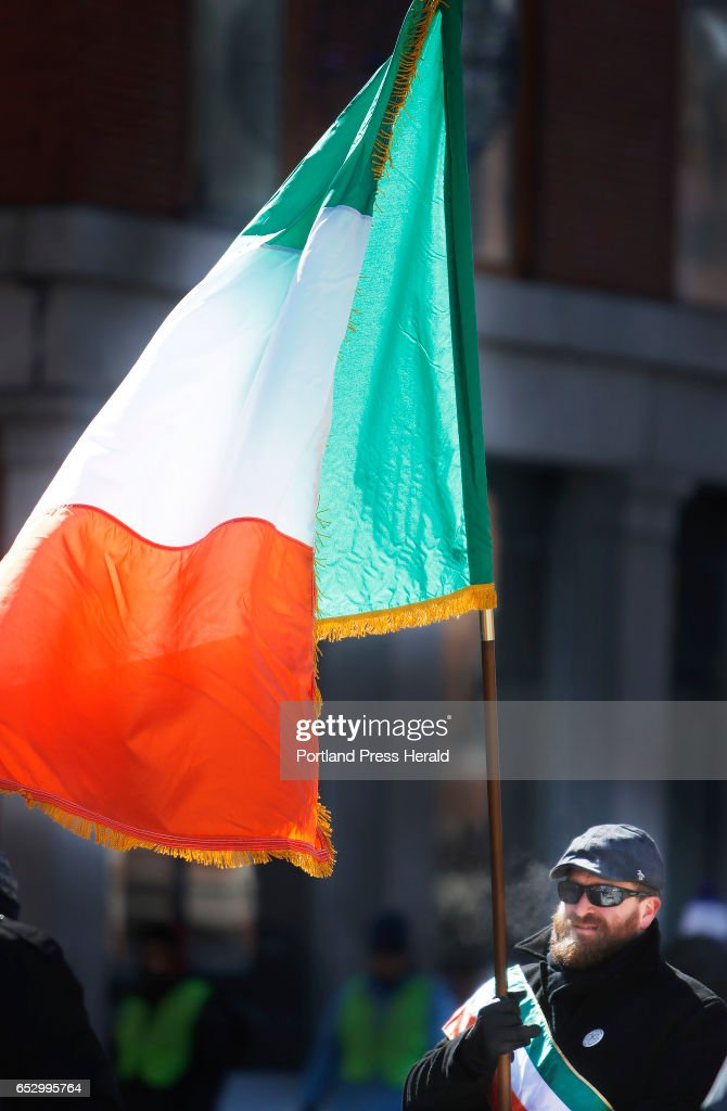 Derek McDonagh of Gorham, originally from Galway, carries the Irish flag while marching with the Ancient Order of Hibernians in the Irish American Club's annual St. Patrick's Parade on Commercial Street.