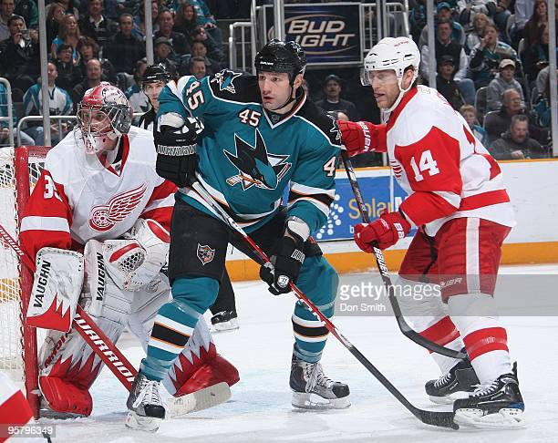 Derek Meech and Jimmy Howard of the Detroit Red Wings defend the net against Jody Shelley of the San Jose Sharks during an NHL game on January 9,...