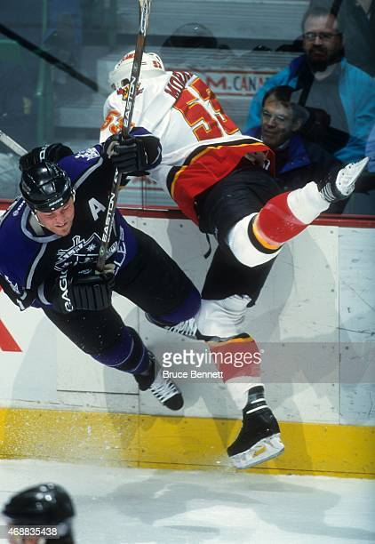 Derek Morris of the Calgary Flames checks Mattias Norstrom of the Los Angeles Kings during an NHL game circa 2000 at the Scotiabank Saddledome in...