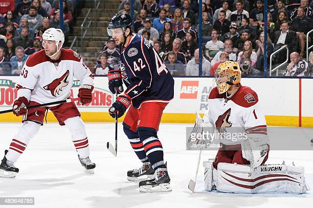 Derek Morris of the Phoenix Coyotes and Artem Anisimov of the Columbus Blue Jackets skate in front of goaltender Thomas Greiss of the Phoenix Coyotes...
