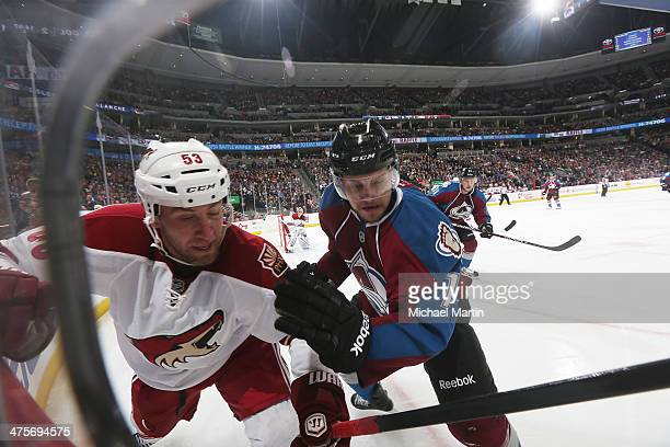 Derek Morris of the Phoenix Coyotes and John Mitchell of the Colorado Avalanche fight for the puck in the corner at the Pepsi Center on February 28,...
