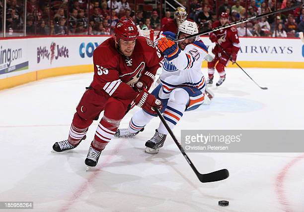 Derek Morris of the Phoenix Coyotes attempts to control the puck under pressure from Luke Gazdic of the Edmonton Oilers during the second period of...