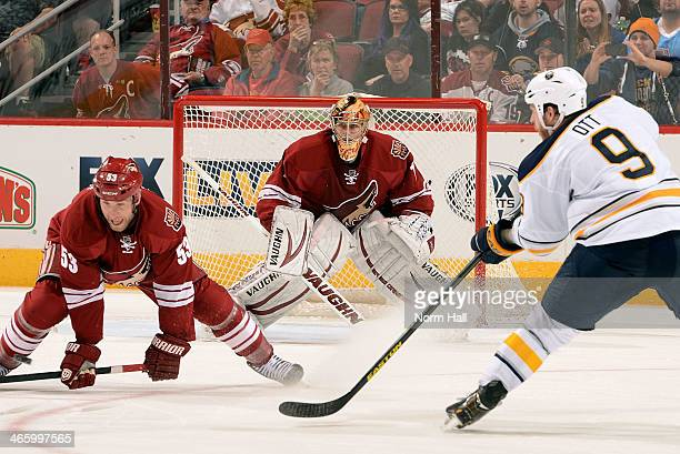 Derek Morris of the Phoenix Coyotes blocks the pass of Steve Ott of the Buffalo Sabres as goaltender Thomas Greiss of the Coyotes follows the action...