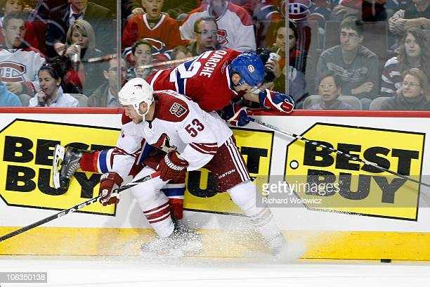 Derek Morris of the Phoenix Coyotes body checks Mathieu Darche of the Montreal Canadiens during the NHL game at the Bell Centre on October 25 2010 in...