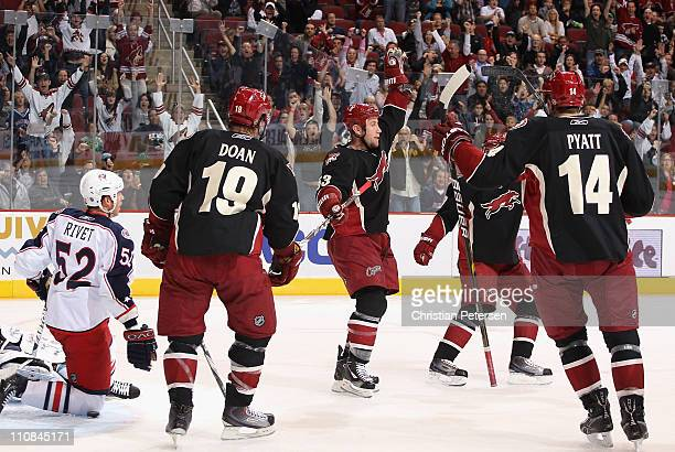 Derek Morris of the Phoenix Coyotes celebrates with teammates Shane Doan and Taylor Pyatt after Morris scored a second period goal against Craig...
