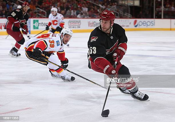 Derek Morris of the Phoenix Coyotes controls the puck ahead of TJ Galiardi of the Calgary Flames during the second period of the NHL game at...